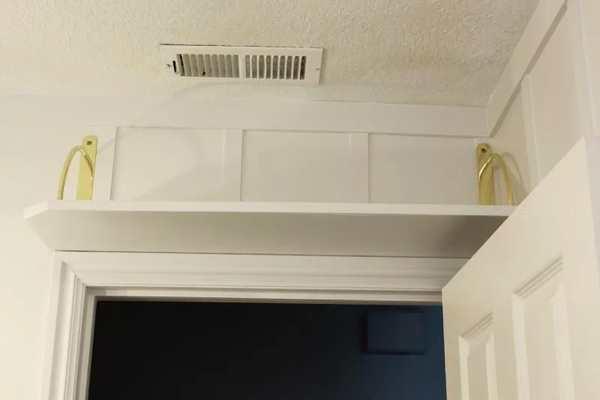 repisa de madera con soportes dorados encima de la puerta